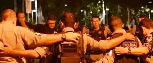 Policiais militares oram em frente ao quartel antes de irem às ruas para combater a criminalidade